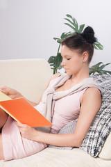Junge Frau sitzt mit Buch auf dem Sofa und liest