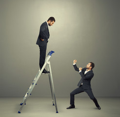 businessman on the stepladder looking down