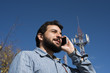Man with hipster style at phone near to antenna