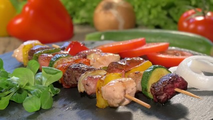 grilled meat skewers on stone plate rotating