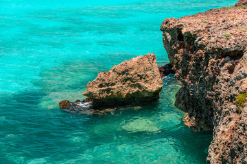 fragment of a cliff sitting in azure turquoise ocean water