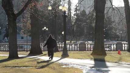 A man walking on a pathway in a city park in the afternoon