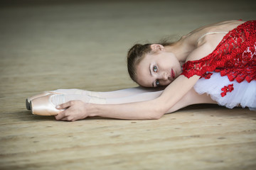 Charming young dancer doing stretching
