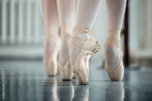 Legs dancers on white pointe, near the choreographic training ma Plakát