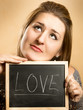 "thoughtful woman holding word ""Love"" written on blackboard"