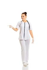 Full length female doctor pointing to the left