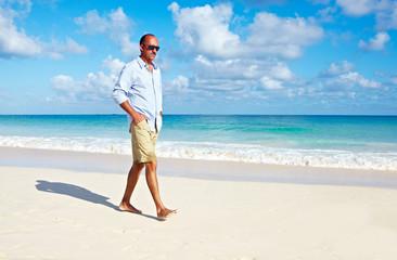 Man walking on sandy beach.
