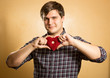 handsome smiling man holding red decorative heart