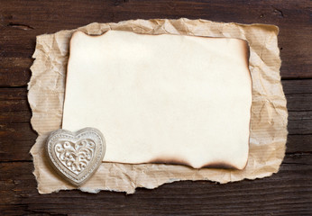 Old paper and  heart on the wood background