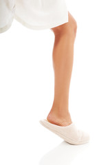 Female foot in white slippers
