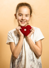 little girl in dress posing with red knitted heart