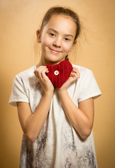 smiling girl hugging red knitted heart