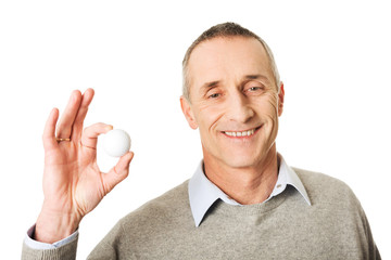 Mature man holding golf ball