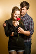 young man embracing girlfriend and giving her red rose