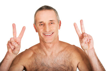 Mature shirtless man with victory sign