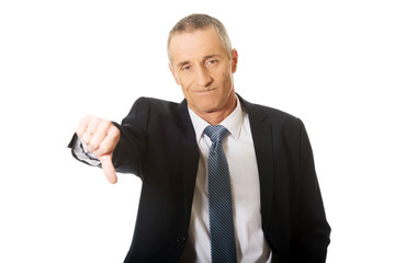 Portrait of businessman showing thumb down sign
