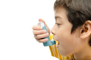 Little boy using Asthma inhaler for breathing on white backgroun
