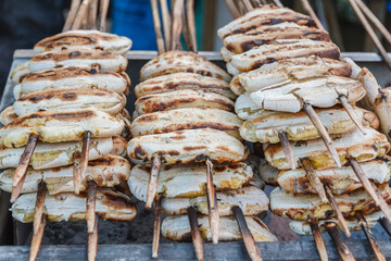 Grilled banana skewers on stove in market. Thailand dessert.