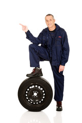 Repairman with leg on a tire pointing to the left