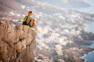 Young woman sitting on rock and enjoying beautiful view