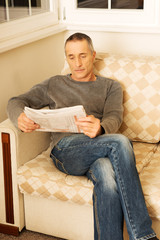 Middle-aged man reading newspaper at home