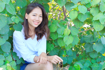 portrait of pretty woman sitting in green leaves bush and smilin