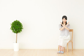 部屋でバツ印する女性