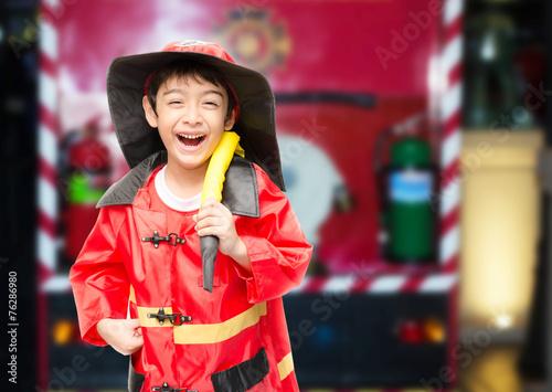 Leinwanddruck Bild Little boy pretend as a fire fighter