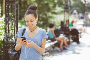 Beautiful Mixed-Race Young Woman Listening Music With Earphones