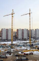 Строительство жилого дома зимой. Два башенных крана
