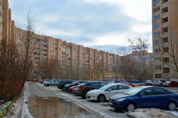 Жилые дома и припаркованные автомобили во дворе зимним днем