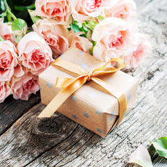 Gift Box and Pink Roses on Wooden Table