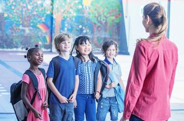 Female teacher explaining to multirace students in schoolyard