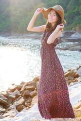 portrait of beautiful woman wearing straw hat and long dress sta