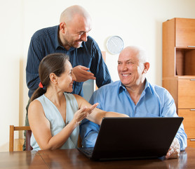 Two men and woman at laptop
