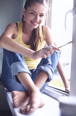 Woman painting wall of an apartment with a paintbrush carefully