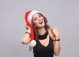 Attractive smiling woman in Santa Cap. Isolated over a gray