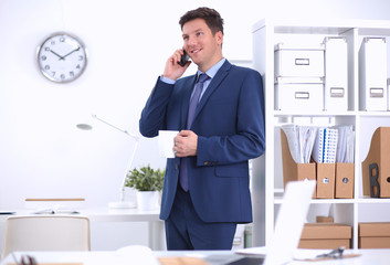 Smiling businessman standing and using mobile phone in office