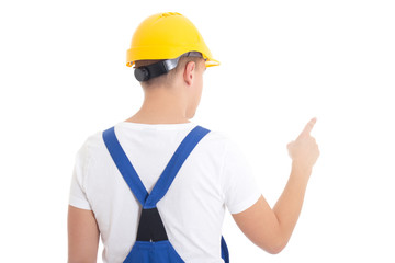 back view of man in  builder uniform and helmet pointing at some