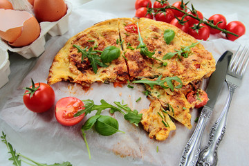 Omelet with fresh eggs with tomatoes and rucola salad leafs