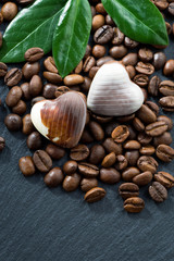 coffee beans and chocolate candies in a heart shape on dark
