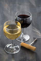 glass of white and red wine on a dark wooden background