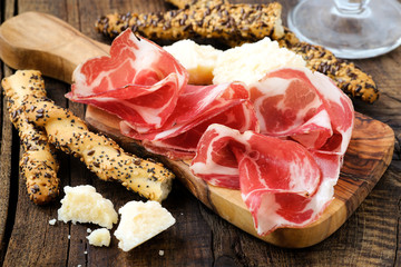 Italian prosciutto or coppa with breadsticks and parmesan