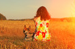 Young woman with dog in the field at sunset light back to camera