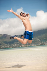 happy man jumping of joy on the beach