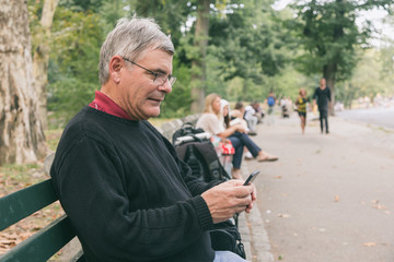 Retired Senior Man at Park, Typing on Mobile, Smiling Expression