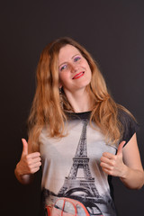 Happy woman smiling and tower Eiffel printed on shirt, ok sign
