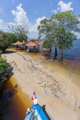Beach with neglected cabins in the middle of Rio Negro, Brazil