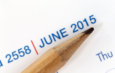The tip of a pencil point to the year 2015 blur Text.
