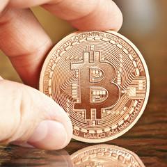 photo of golden bitcoins (virtual coins) in a hand.